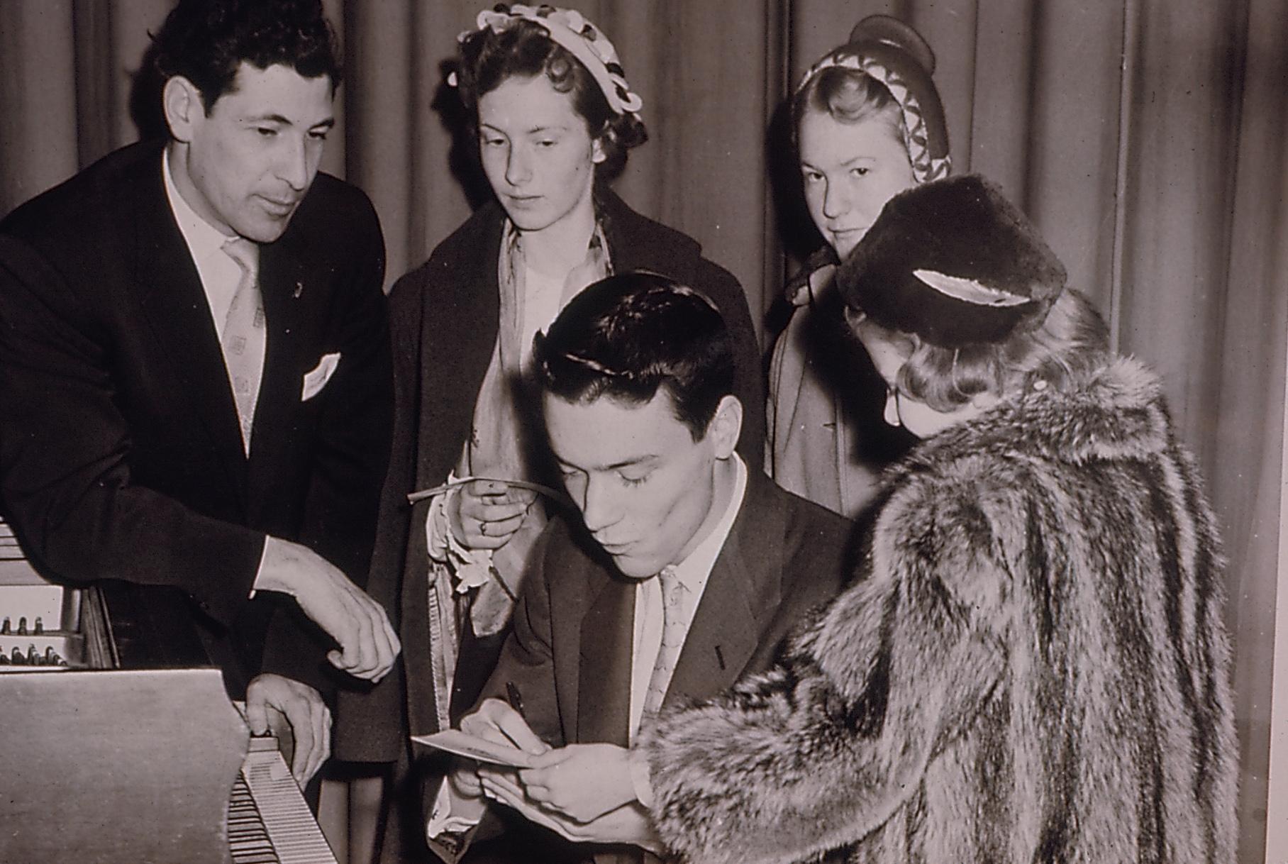 Un pianiste donne des autographes à de jeunes fans avec Gilles Lefebvre en 1950.  Fonds Centre d'arts Orford. La Société d'histoire de Magog